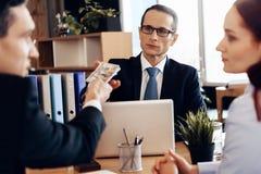 Den vuxna säkra mannen ger pengar till advokaten för skilsmässa som sitter på kontorstabellen Arkivfoto