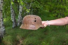 In den Wald den deutschen Sturzhelm M35 graben nachgemacht Wiederaufnahme WW2 Russland stockfotografie