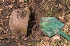 In den Wald den deutschen Sturzhelm M35 graben nachgemacht Wiederaufnahme WW2 Russland lizenzfreie stockfotos
