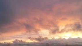 In den Wolken, die den Sonnenuntergang aufpassen Lizenzfreie Stockfotos