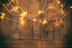 Den Wood brädetabellen av jul värme framme guld- girlandljus på trälantlig bakgrund blänka samkopieringen royaltyfri foto