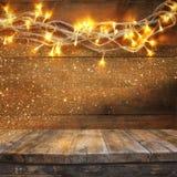 Den Wood brädetabellen av jul värme framme guld- girlandljus på trälantlig bakgrund Filtrerad bild Selektivt fokusera fotografering för bildbyråer