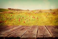 Den Wood brädetabellen av sommarlandskapet av fältet med många blommar framme Bakgrund är suddig royaltyfri bild