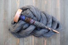 Den Wood droppspindeln på en hög av att ströva för ull vred med garn Royaltyfria Foton
