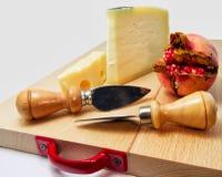 Den Wood skärbrädan med sortimentet av ostar och granatäpplet bär frukt för matbegrepp Arkivbild