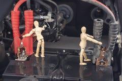 Den Wood skyltdockan reparerar begrepp för arbete för bilbatteri Royaltyfri Foto