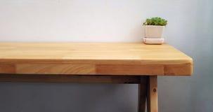 Den Wood tabellen med det gröna trädet på blomkruka- och cementväggen lämnade Co arkivfoton