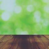Den Wood tabellen och den abstrakta naturen för bokeh gör grön bakgrund Arkivbild