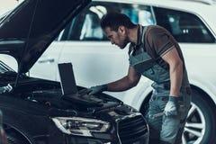 Den Working In Auto för bilmekanikern reparationen shoppar royaltyfri foto