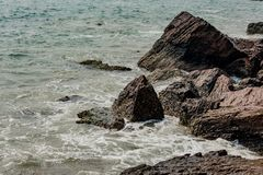 Den Yarada stranden med indiska havvågor som kraschar på kusten, vaggar och stenar Det långa exponeringsskottet med silkeslent sl arkivbilder