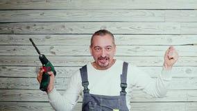 Den Yfppy byggnadsarbetaren med borrar in hans hand lager videofilmer