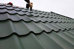 Den yrkesmässiga arbetaren arbetar på installation av ett tak av ett tak vid ark av en metalltegelplatta och borrar en skruv med  fotografering för bildbyråer