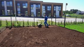 Den yrkesmässiga arbetarmannen drar gräsmattarullen för slätar gårdjord ut Gimbalrörelse arkivfilmer
