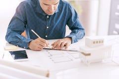 Den yrkesmässiga arkitekten som arbetar på kontorsskrivbordet, drar han med en linjal på ett utkastprojekt, en arkitektur och ett royaltyfri foto
