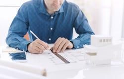 Den yrkesmässiga arkitekten som arbetar på kontorsskrivbordet, drar han med en linjal på ett utkastprojekt, en arkitektur och ett arkivbilder