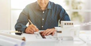 Den yrkesmässiga arkitekten som arbetar på kontorsskrivbordet, drar iscensätter han med en linjal på ett utkastprojekt, arkitektu royaltyfria foton