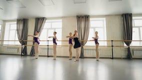 Den yrkesmässiga balettläraren undervisar små flickor att vända på tåspetsarna, och stretcg lägger benen på ryggen och armar meda stock video