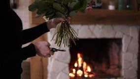 Den yrkesmässiga blomsterhandlaren klipper stammarna av blommor i buketten Kvinnan i svart monterar en perfekt bukett sista touch arkivfilmer