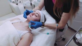 Den yrkesmässiga cosmetologisten gör vakuummassage för ansiktsbehandling LPG till en härlig kvinnlig patient Föryngringtillvägagå arkivfilmer