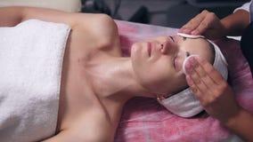 Den yrkesmässiga cosmetologisten tonar framsidan för kvinna` s genom att använda bomullssvampen Den unga kvinnan ligger på soffan lager videofilmer
