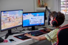 Den yrkesmässiga datorspelaren spelar på en dator genom att använda två bildskärmar fotografering för bildbyråer
