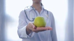 Den yrkesmässiga dietitianen med det gröna äpplet i händer ger in i kamera att råda som är sunt, bantar för wellness, på vitt lager videofilmer
