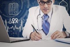 Den yrkesmässiga doktorn skriver medicinrecept Arkivfoto