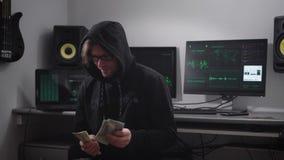 Den yrkesmässiga en hacker betraktar hans pengar misshas som ser kameran och lägger ibland därefter, ner en bunt in lager videofilmer