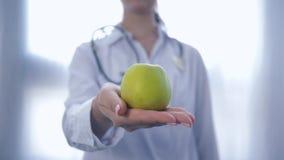 Den yrkesmässiga experten på mat med det gröna äpplet i händer ger in i kamera att råda som är sunt, bantar för wellness, unfocus stock video
