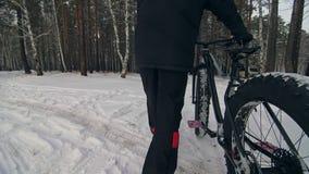 Den yrkesmässiga extrema idrottsmancyklisten går med den feta cykeln i det fria Cyklisten som går i mannen för vintersnöskogen, g arkivfilmer
