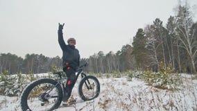 Den yrkesmässiga extrema idrottsmancyklisten står en fet cykel i utomhus- Cyklisten vilar i mannen för vintersnöskogen går stock video