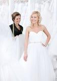 Den yrkesmässiga formgivaren och bruden undersöker klänningen Arkivbilder
