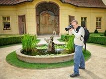 Den yrkesmässiga fotografen med ryggsäcken och DSLR i barocken arbeta i trädgården Royaltyfri Foto