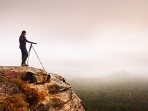 Den yrkesmässiga fotografen tar foto av det dimmiga landskapet med den spegelkameran och tripoden Arkivfoton