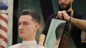 Den yrkesmässiga frisören visar den tillbaka sikten av frisyren genom att använda spegeln till den stiliga tillfredsställda manli stock video