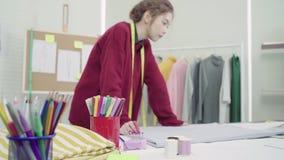 Den yrkesmässiga härliga asiatiska kvinnliga modeformgivaren som arbetar med tyg, skissar och drar bekläda design på studion arkivfilmer