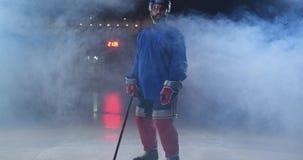Den yrkesmässiga hockeyspelaren med en pinne accelererar på isen och stoppen plötsligt som är främsta av se för kamera stock video