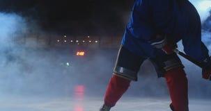 Den yrkesmässiga hockeyspelaren med en pinne och en puck flyttar sig på Luda i skridskor och hjälm på en mörk bakgrund och rök arkivfilmer