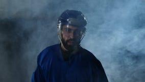 Den yrkesmässiga hockeyspelaren med en pinne och en puck flyttar sig på Luda i skridskor och hjälm på en mörk bakgrund och rök lager videofilmer