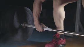 Den yrkesmässiga idrottsmannen lyfter en tung skivstång arkivfilmer
