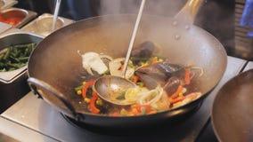 Den yrkesmässiga kocken steker musslor och räkor med grönsaker på gatamatfestivalen Grillat räkor och blötdjur stock video