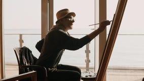 Den yrkesmässiga konstnären är förlovad i teckningssammanträde på en stol vid havet arkivfilmer
