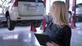 Den yrkesmässiga kvinnliga mekanikern använder minnestavladatoren i en automatisk reparation shoppar på bakgrund av bilar på hydr stock video