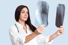 Den yrkesmässiga kvinnliga radiologen med förvånat uttryck, jämför två x-strålar, kan ` t göra beslut omkring att diagnostisera,  fotografering för bildbyråer