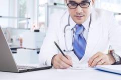 Den yrkesmässiga läkaren gör medicinrecept Arkivbild