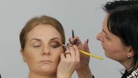 Den yrkesmässiga ledar- makeupkonstnären applicerar beige ögonskugga med den speciala borsten på modellöga på slutet för skönhets lager videofilmer