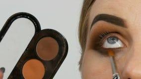 Den yrkesmässiga ledar- makeupkonstnären applicerar den beigea ögonskuggapaletten med den speciala borsten på modellöga på slutet arkivfilmer