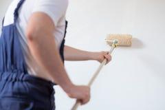 Den yrkesmässiga målarearbetaren målar en vägg fotografering för bildbyråer