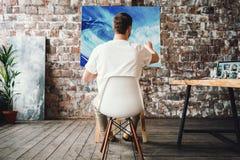 Den yrkesmässiga målaren sitter på stol framme av staffli med kanfas, hållmålarpensel, i hand och att dra olje- målning Konstnära arkivbild