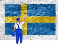Den yrkesmässiga målaren täcker tegelstenväggen med flaggan av Sverige Arkivfoto